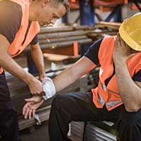 Manual worker assisting his colleague with physical injury in steel mill